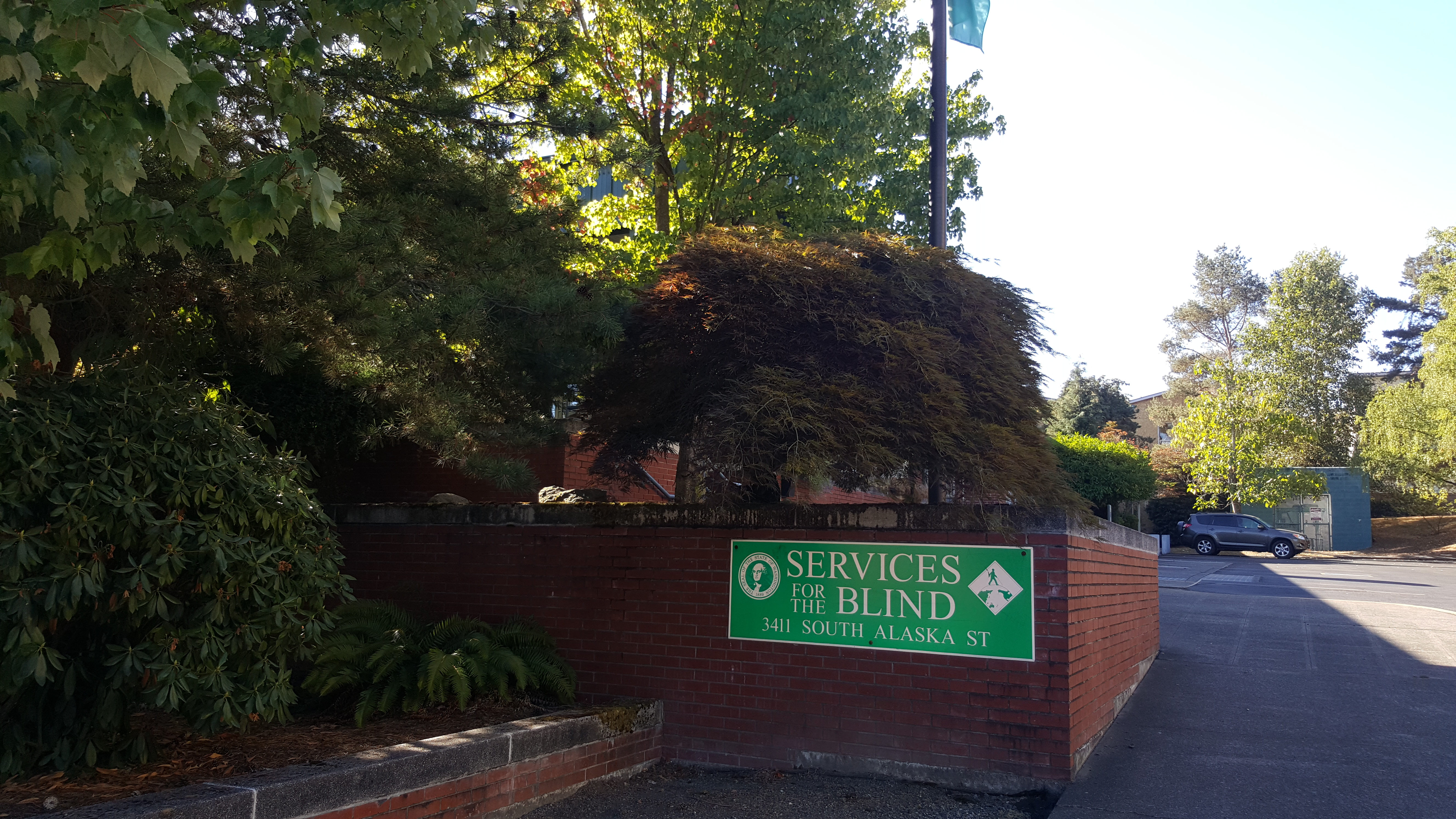 Exterior of Department of Services for the Blind's Seattle Office on a sunny day.  It is a red brick building with flowering bushes and shrubs in front.