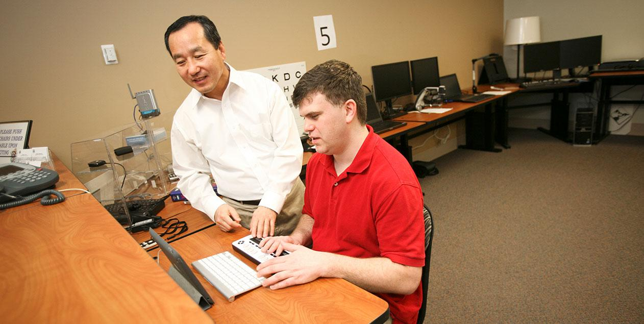 A man working at a desk using a tablet. Another man is instructing him on the use of the wireless braille display.